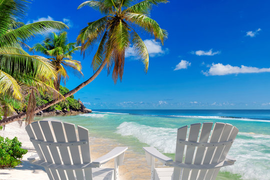 Beach chairs on sandy beach with palm and turquoise sea.  Summer vacation and travel concept.