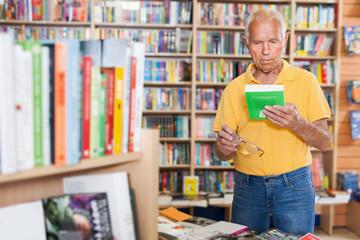 Focused senior man choosing book at bookshelves in bookshop