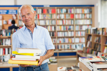 Positive aged man buyer holding pile of books in bookstore