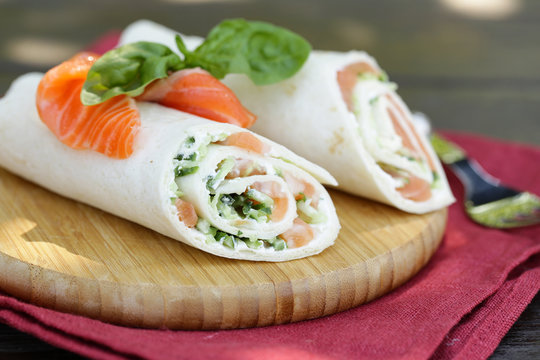 tortilla with a red fish vegetables and salad