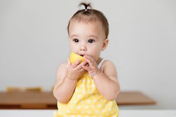 Baby girl chewing on a lemon