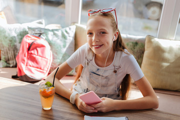 Relaxing girl. Beautiful beaming girl wearing stylish clothes relaxing while listening to music