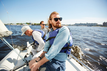 Deurstickers Zeilen Content carefree young bearded man in sunglasses enjoying yachting with friends: he sitting on deck and contemplating seascape