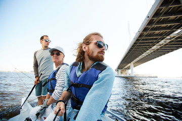 Foto auf AluDibond Segeln Pensive dreamy men of different ages sailing yacht together and enjoying floating on river, they looking around