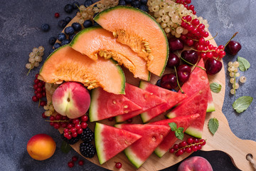 Fresh summer fruits and berries, slices of watermelon and cantaloupe on a round cutting board, raw vegan eating, vitamins and diet concept