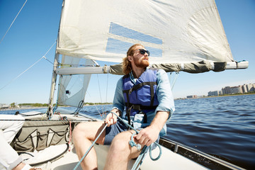Foto op Aluminium Zeilen Serious pensive hipster young man with beard holding rope while operating sail boat and enjoying landscape around