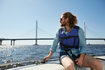 Serious thoughtful handsome young guy with beard wearing sunglasses and life jacket admiring waterscape sitting on boat deck and holding railing