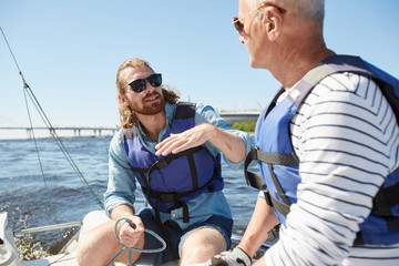 Content handsome young bearded man in sunglasses wearing life jacket gesturing while explaining sailing rules to mature man during sailing tour