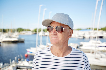 Smiling content mature man in cap and sunglasses wearing striped sweater contemplating around while resting in yacht club