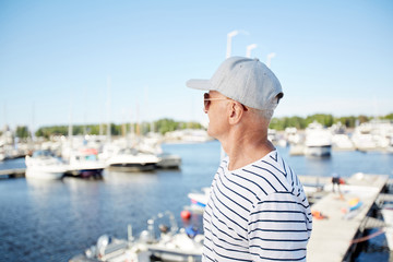 Pensive dreamy mature man in cap and sunglasses being on vacation looking at sailboats while standing on pier in yacht club