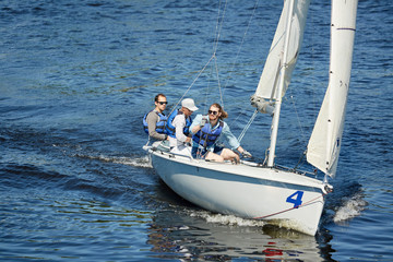 Group of free yachtsmen in sunglasses and life jackets sitting on sailboat deck and contemplating around while sailing at competition