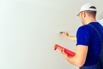 Painter man at work with a paintbrush. Home renovation and decoration concept.