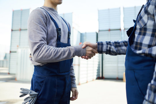 Close-up of unrecognizable foreman and new mover in workwear making handshake in outdoor cargo warehouse, man hiring new mover at cargo storage