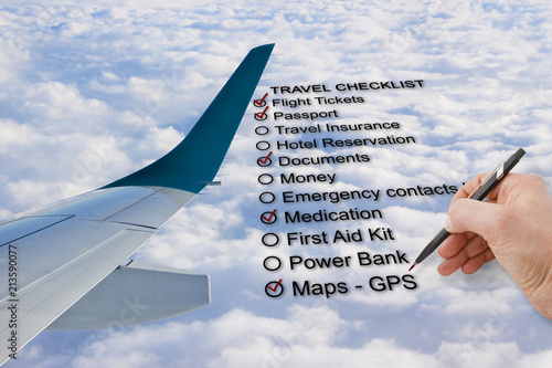hand write a travel checklist over a cloudy sky and airplane