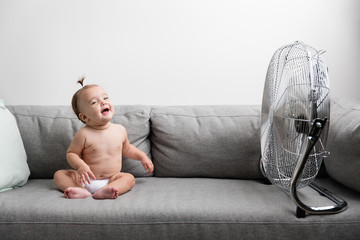 Laughing baby girl sitting on sofa next to fan