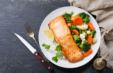 plate of baked salmon steak with vegetables