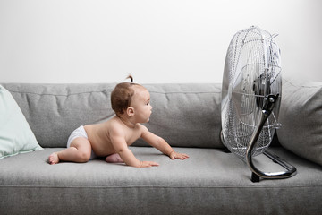 Baby chilling on sofa facing fan