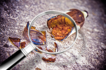 The search for the causes of alcoholism - Shattered beer bottle resting on the ground seen through a magnifying glass - concept image