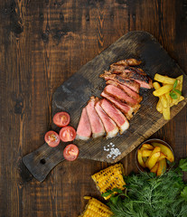 grilled steak on a cutting board on a wooden background. Top view.