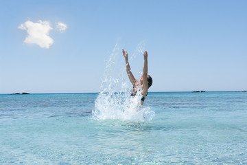 Woman enjoys cool sea water and splashing, summer in Greece