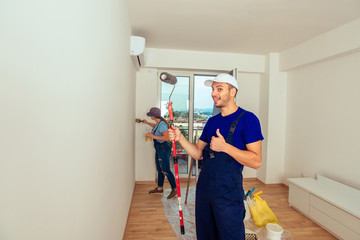 Young couple painting wall at home. Home renovation and refurbishment concept.