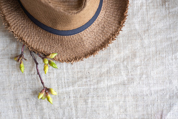 Top view of Summer brown panama straw hat with flower plant on linen cloth.travel concept.copy space for adding text.