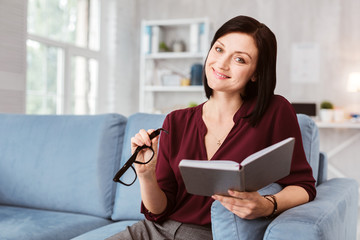 Cheerful woman. Cheerful calm woman smiling happily and holding her glasses while sitting with a notebook and planning her working day
