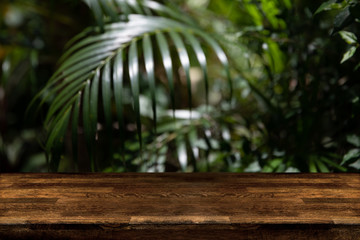 Dark wood table top with blur on green palm leaves or tree in tropical forest. Background usage or product presentation.