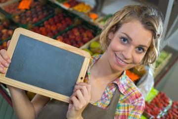 Greengrocer holding blank slate