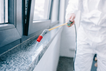 cropped image of pest control worker spraying pesticides on windowsill at home