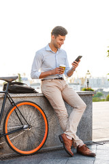 Happy young stylish man using mobile phone