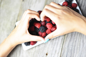 Woman hands in form of a heart over a plate with mixed berries