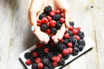 Woman hand holding red ripe raspberries and blackberries, fresh fruits for a healthy lifestyle