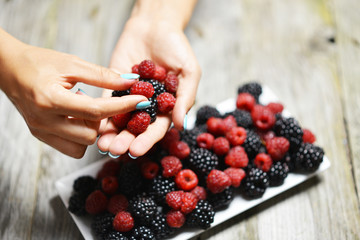 Woman picking mixed fresh berries from white plate with blackberries and raspberries