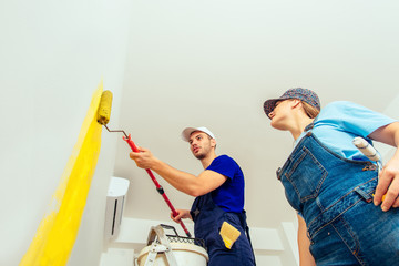 Portrait Of Young Couple Who Paint Walls With Paint Roller. Young family renovating their new apartment concept.