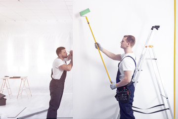 Decorators painting a wall with a roller in a renovating office