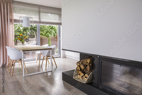 Fireplace Next To White Chairs At Table In Bright Dining Room Interior With Window Real