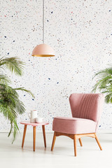Pink lamp above table and armchair in patterned living room interior with plants. Real photo