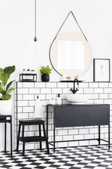 Plants and mirror in black and white bathroom interior with checkered floor and stool. Real photo