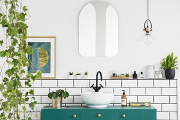 Mirror on white wall above green washbasin in bathroom interior with plants and poster. Real photo