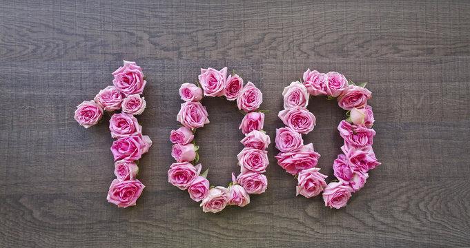 100 (one hundred) - vintage number of pink roses on the background of dark wood - for congratulations, postcards, websites, design, printing
