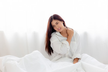 Healthy concept. Attractive beautiful woman sprain neck, shoulder. Lovely woman slept on her neck wrong. Pretty girl wakes up in the morning on bed with painful neck. She looks suffering. copy space