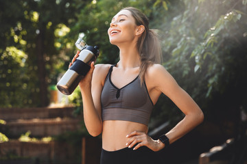 Cheerful young fitness girl drinking water