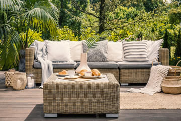 Rattan table and pillows on couch on patio in the garden during summer. Real photo
