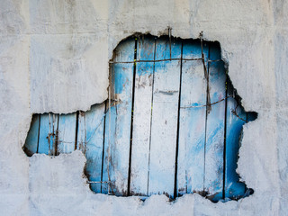 Photo of concrete wall with hole and blue fence