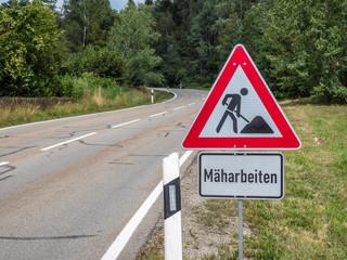 Warnschild Mäharbeiten auf einer Landstraße