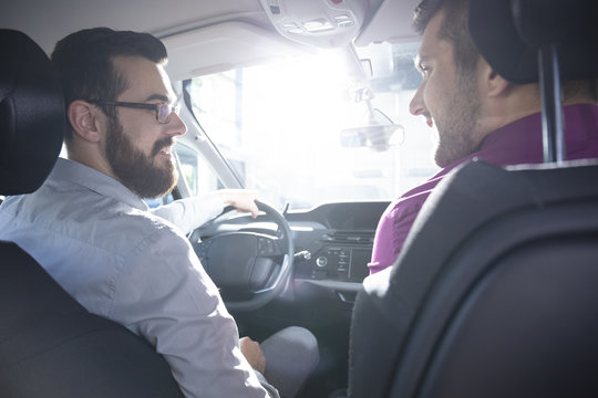 Smiling buyer and dealer during a test drive in a exclusive car