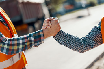 Close-up of two workers giving a handshake