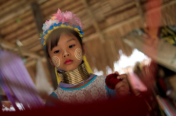 An Ethnic Kayan also know as a Long Neck girl sits at her parents souvenir shop in the Kayan village at the northern province of Chiang Rai
