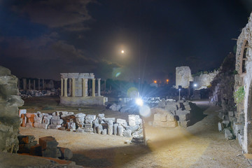 beautiful night view of the ruins of the trading Agora in front of the amphitheater with illumination. full moon and clouds in the sky. Side, Turkey